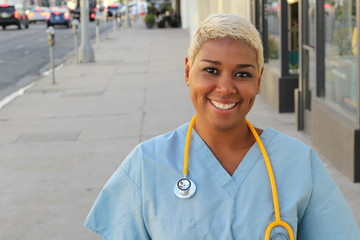 Young happy afro american nurse standing outside of the hospital in the city streets. Smiling, looking at camera.