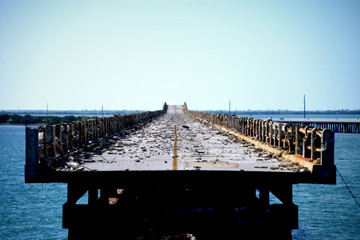 Abandoned, desolate bridge over the ocean cut off from civilization