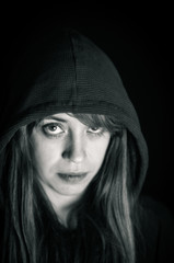 Close-Up Portrait Of Serious Woman In Hooded Shirt Against Black Background