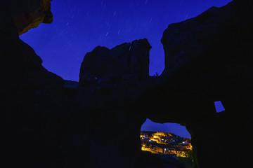 tarihi kalıntılar arasından gökyüzü yıldızları ve şehir manzarası