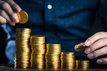 金貨を積み上げる人の手