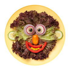 Smiling face made of vegetables on plate