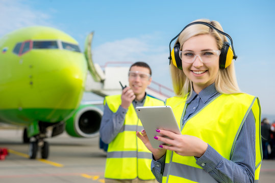 Airport workers with airplane on the background