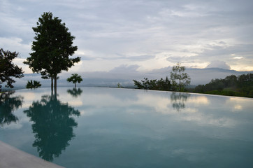 Edgeless pool and tree reflection mountain background