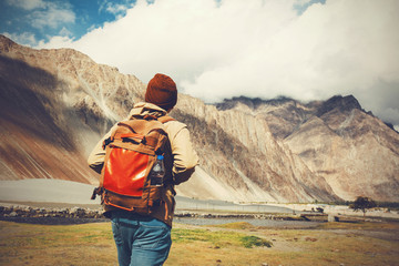 Back of young travel backpacker walking towards the highland mountain. Wall mural