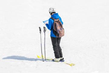 Skifahrer mit Helm orientiert sich auf einer Karte