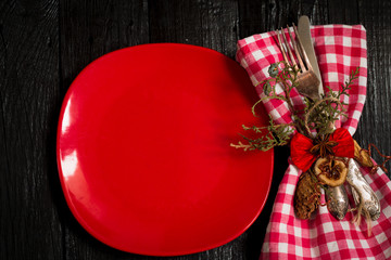 Beautiful Christmas Cutlery on a napkin in red and white checkered with   plate.   black wooden background.