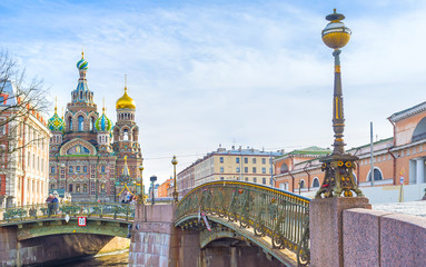 : The scenic old fashioned streetlight on Malokonushenny bridge with the Church on Spilled Blood on the background