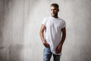 Handsome bearded man in white blank t-shirt on grey background