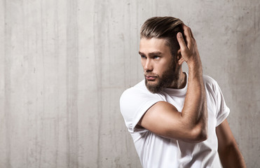 Handsome bearded man in a blank white t-shirt with stylish hair on a cement wall