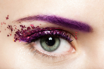 Foto op Plexiglas Beauty Close-up of a woman's open eye with a shiny trendy makeup in violet tones with sparkles