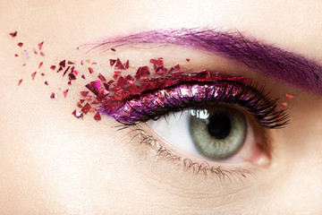 Foto op Plexiglas Beauty Woman's eye with a shiny trendy makeup in violet tones with sparkles