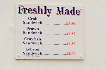 Menu sign on wall outside Seafish food kiosk