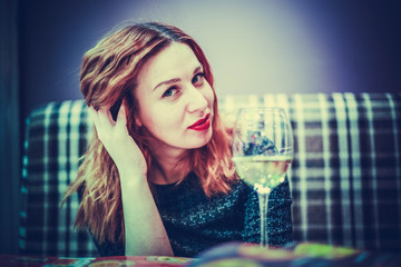 Young woman with red hair in a restaurant  the menu and glass of wine