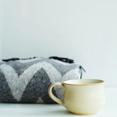 Warm grey plaid and cup of coffee or tea over white background
