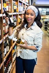 Woman looking at wine bottle in grocery section at supermarket