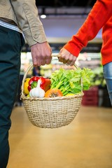 Couple holding a basket of vegetables in super market