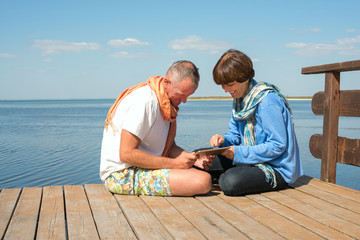 Couple communicate with friends using tablet pc