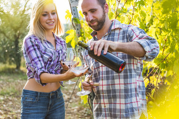 Man Pouring Wine to his Girlfriend in Glass during Grape Harvest