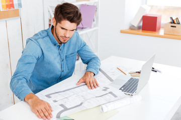 Man looking at diagrams on the table