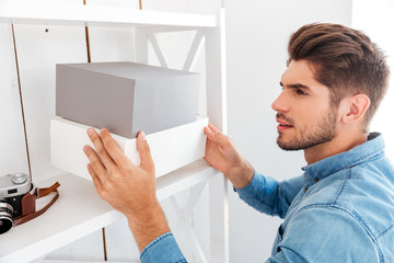 Hanadsome young man putting boxes on the shelf