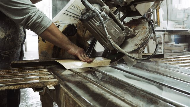 Worker uses saw machine for cutting marble stone piece , close up