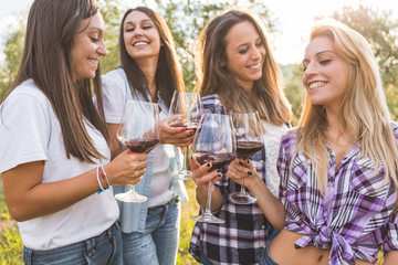 Smiling Girls Toasting with Red Wine Outdoors