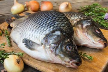 Fresh raw carp on cutting board, rosemary, onions, natural light