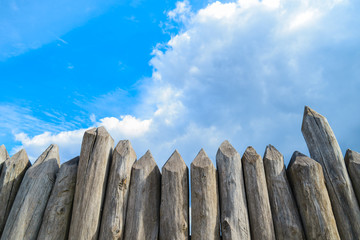 wooden palisade on the background of blue sky