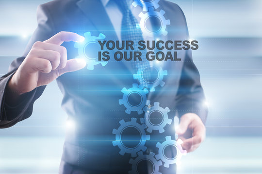 """Businessman is selecting """"Your success is our goal"""" on the virtual screen."""