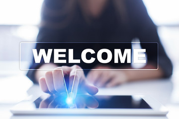 """Woman is using tablet pc, pressing on virtual screen and selecting """"Welcome""""."""