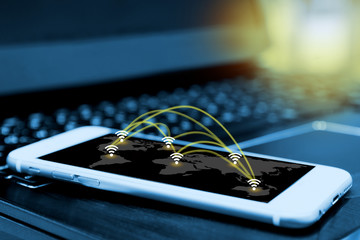 Wifi icon and network connection concept and smartphone screen with blur laptop background , wireless communication network , internet of things , flare light