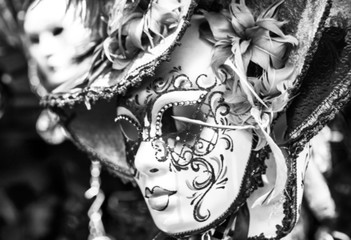 Blurred Venetian masks in store display in Venice. Annual carnival in Venice is among the most famous in Europe. Black-white photo as conceptual background.