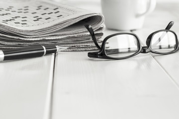 Stack of newspapers with eyeglasses and coffee