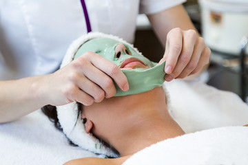 Beautiful young woman with antiaging facial mask in spa.