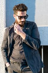 young man bearded outdoor posing smoking