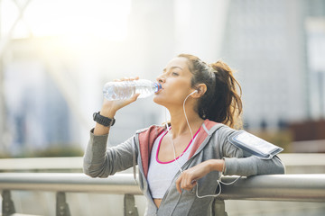 Woman runner is having a break and drinking water