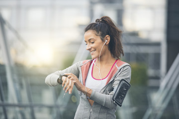 Female runner looking at her sport watch. Measuring heart rate