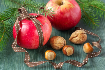 Christmas food background. Apples with nuts on wooden table. Vintage style.