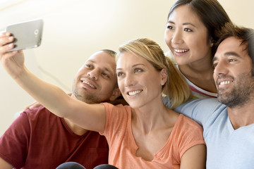 Group of friends taking selfie pictures with smartphone
