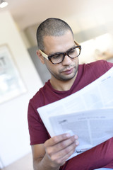 Portrait of hispanic guy with eyeglasses reading newspaper