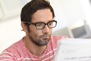 Portrait of man at home reading newspaper