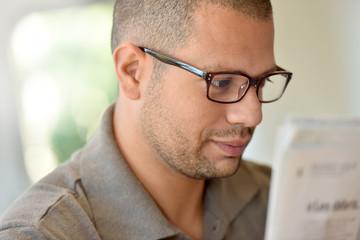 Portrait of hispanic guy with eyeglasses reading newspaper