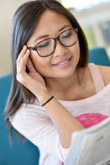 Portrait of young asian girl with eyeglasses reading newspaper