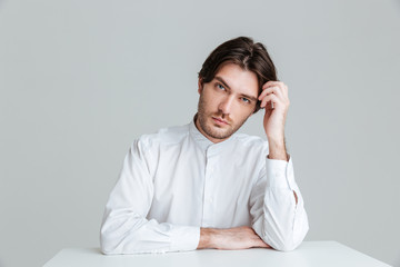 Thoughtful young man in white shirt sitting at the table