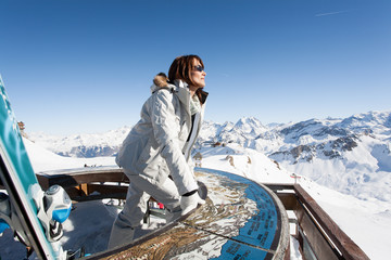 femme au sommets des montagnes enneigées devant une table d'orientation