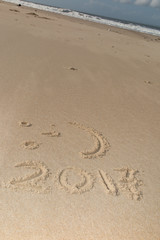 Digits 2017 on the sand seashore - concept of new year