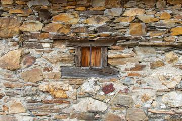Pequeña ventana de madera en construccion rural de piedra