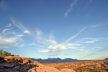 Desert sunset wide angle with mountains in background and clouds and brush and moon