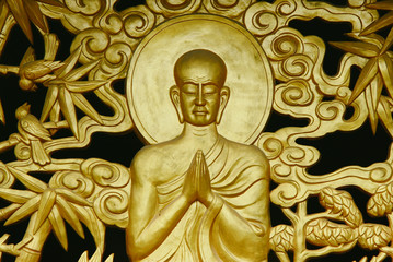 Golden-painted relief image of a meditating Buddha on the wall of a Buddhist pagoda in Vietnam.